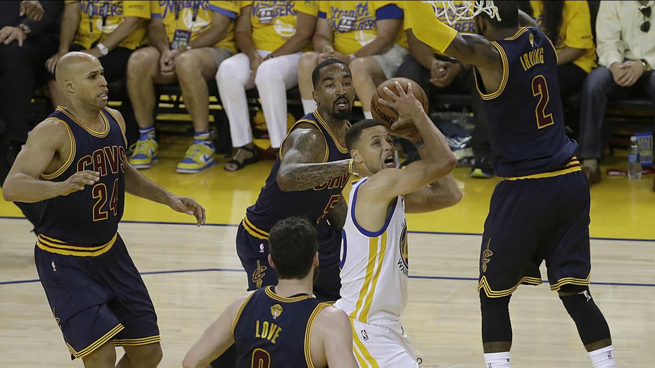 Warriors' Stephen Curry shoots between Cavaliers defenders during Game 2 of basketball's NBA Finals in Oakland, Calif., on June 5, 2016. (AP Photo/Marcio Jose Sanchez)