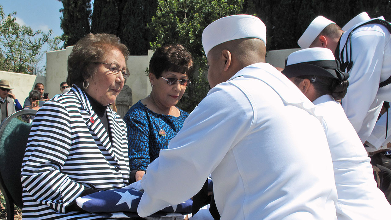 Helen Chavez, the widow of Cesar Chavez receives a flag from the U.S. Navy, honoring her husband's military service during a ceremony in Keene, Calif., Thursday, April 23, 2015.