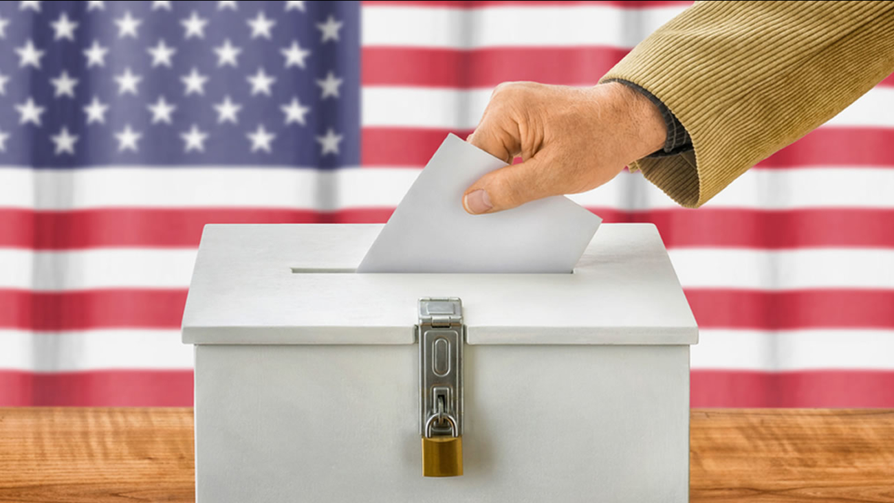 A voter places their ballot into a box.