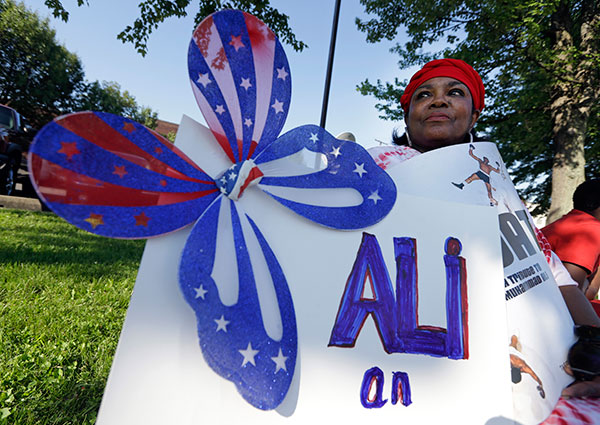 <div class='meta'><div class='origin-logo' data-origin='none'></div><span class='caption-text' data-credit='Michael Conroy/AP Photo'>Frances Woods holds a sign saluting Muhammad Ali as she awaits his funeral procession to make its way down Muhammad Ali Boulevard in Louisville, Ky. Friday, June 10.</span></div>