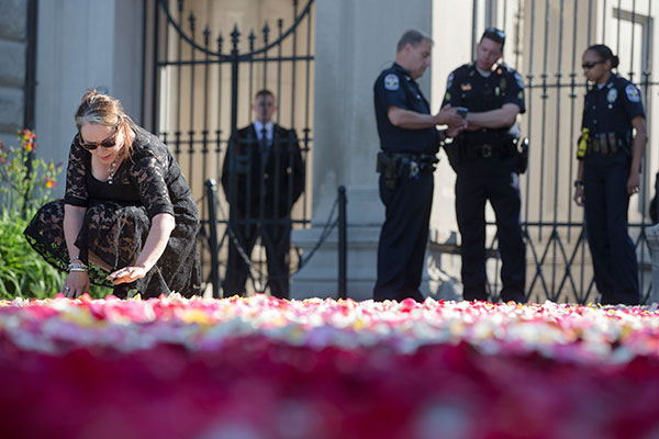 <div class='meta'><div class='origin-logo' data-origin='none'></div><span class='caption-text' data-credit='John Minchillo/AP Photo'>Maggie Cassaro, of Louisville, spreads roses along the entrance way to Cave Hill Cemetery as police stand guard before the arrival of Muhammad Ali's funeral procession.</span></div>