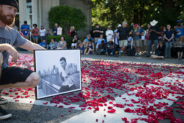 <div class='meta'><div class='origin-logo' data-origin='none'></div><span class='caption-text' data-credit='John Minchillo/AP Photo'>Nick Smith, of Louisville, poses for a photograph holding a drawing of Muhammad Ali as spectators wait for the arrival of Ali's funeral procession to enter Cave Hill Cemetery.</span></div>