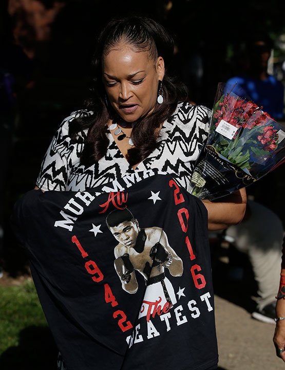 <div class='meta'><div class='origin-logo' data-origin='none'></div><span class='caption-text' data-credit='Darron Cummings/AP Photo'>Robin Marshall holds a t-shirt and flowers as she waits for the procession to pass with the hearse carrying the body of Muhammad Ali, Friday, June 10, 2016, in Louisville, Ky.</span></div>