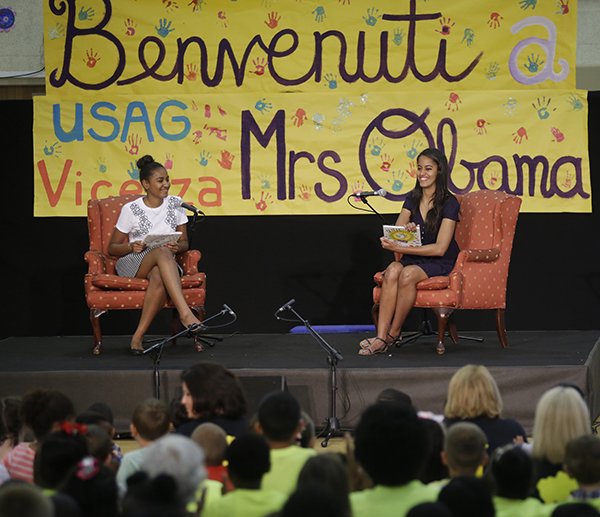 <div class='meta'><div class='origin-logo' data-origin='none'></div><span class='caption-text' data-credit='AP'>Sasha and Malia Obama, show books to children during a visit to soldiers and their families at the U.S. Army Garrison Vicenza June 19, 2015.  (AP Photo/Antonio Calanni)</span></div>