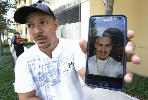 <div class='meta'><div class='origin-logo' data-origin='none'></div><span class='caption-text' data-credit='AP'>Angel Mendez, standing outside the Orlando Regional Medical Center, holds up a cell phone photo trying to get information about his brother Jean C. Mendez.</span></div>