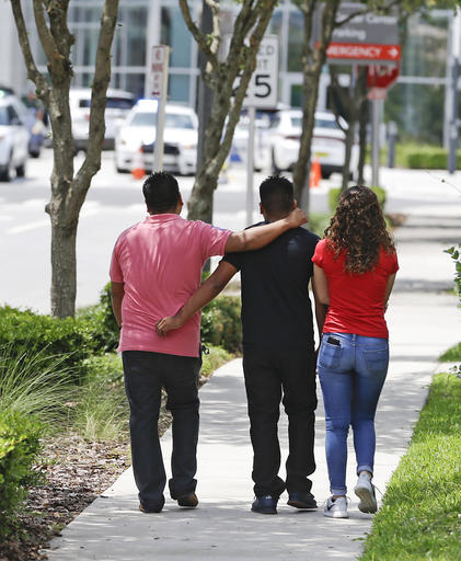 <div class='meta'><div class='origin-logo' data-origin='none'></div><span class='caption-text' data-credit='AP'>A group of people walk to the emergency room of Orlando Regional Medical Center a</span></div>