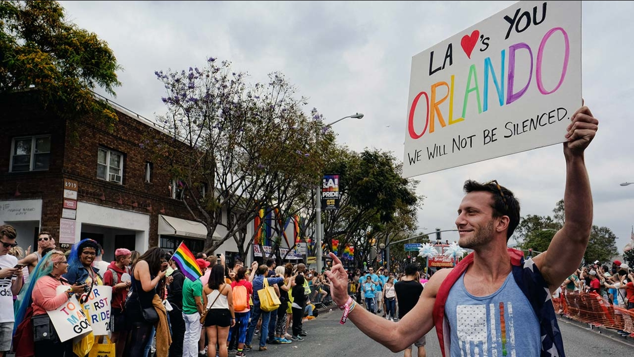 Branden Joyce holds a sign in support of the shooting victims in Orlando, during the gay pride parade in West Hollywood, Calif. on Sunday, June 12, 2016.