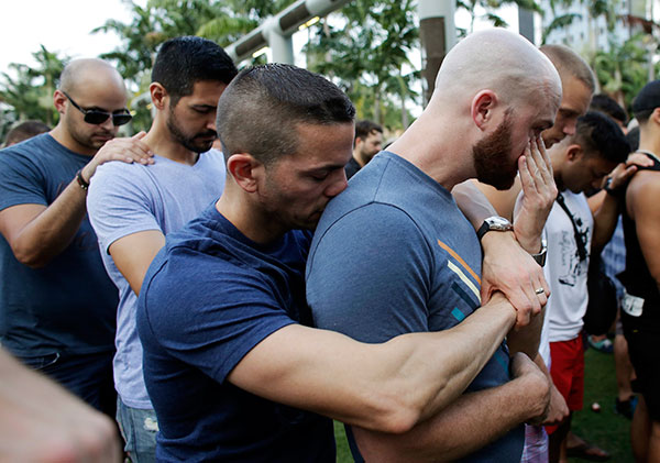 <div class='meta'><div class='origin-logo' data-origin='none'></div><span class='caption-text' data-credit='Lynne Sladky/AP Photo'>Caleb McGrew, right, wipes tears as he stands with his partner Yosniel Delgado Giniebra, center, during a vigil in Miami Beach, Fla.</span></div>