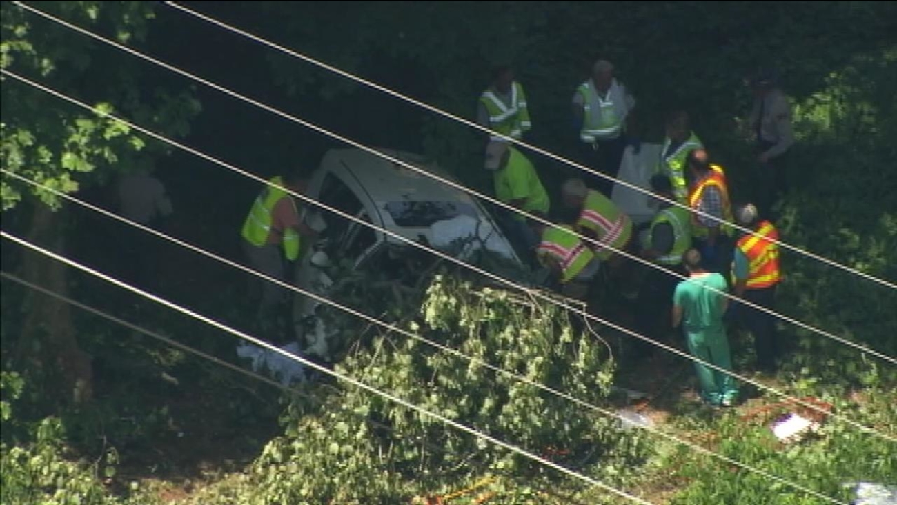 Officials work at the scene where the SUV went off the road.