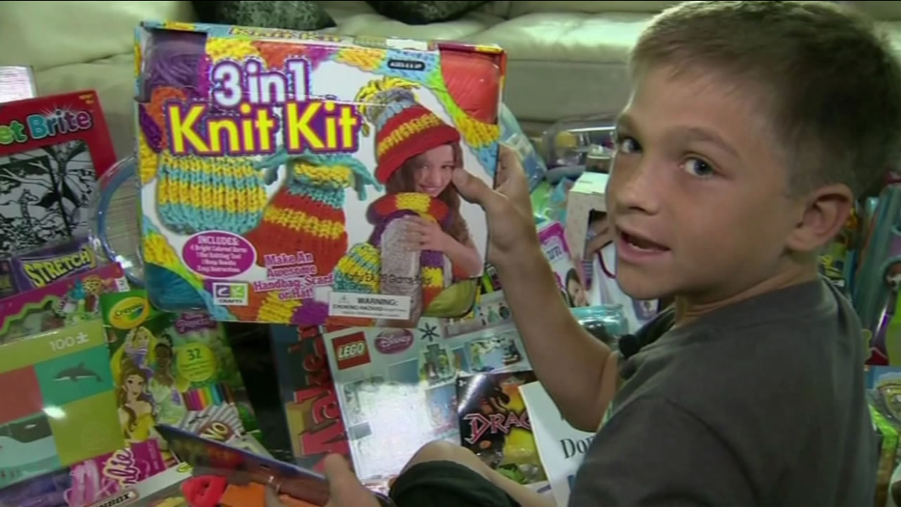 This image shows 10-year-old Kadin Hoven with a pile of toys after launching a toy drive for Mattel Children's Hospital at UCLA, the same hospital where he is receiving treatment.