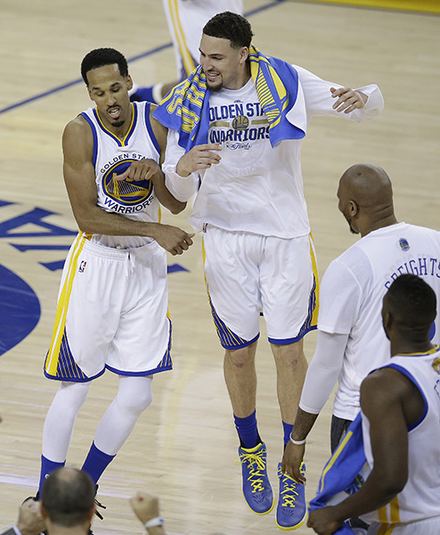 Golden State Warriors guard Shaun Livingston, left, and guard Klay Thompson celebrate during the second half of Game 1 of basketball's NBA Finals.