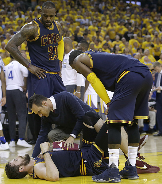 A trainer checks on Cleveland Cavaliers forward Kevin Love, bottom, as forward LeBron James and guard Kyrie Irving watch during the first half of a Game 2 of the NBA Finals