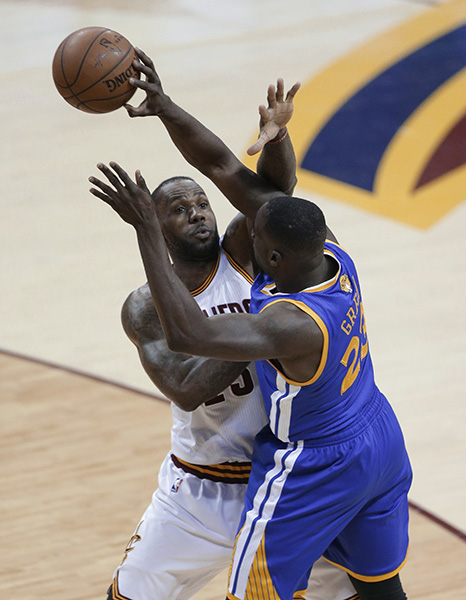 Cleveland Cavaliers forward LeBron James, left, defends Golden State Warriors forward Draymond Green during the first half of Game 3 of basketball's NBA Finals.