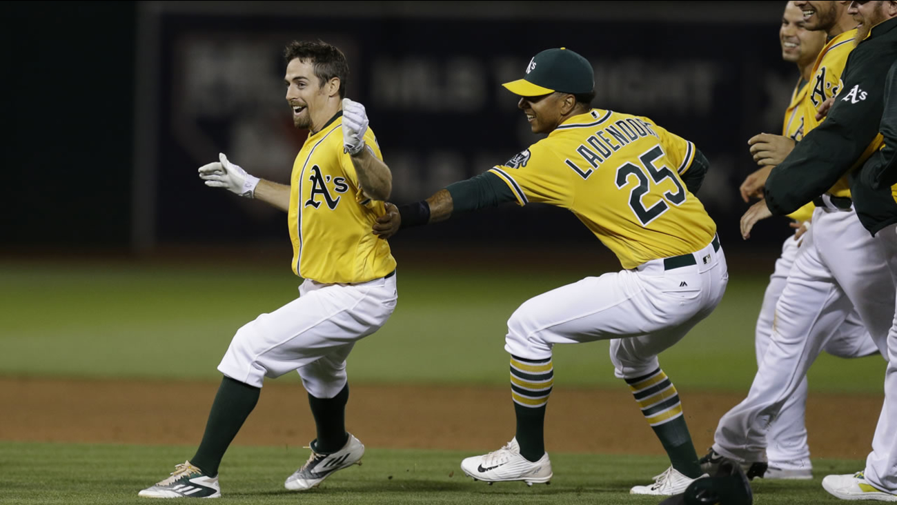Oakland Athletics' Billy Burns, left, celebrates with Tyler Ladendorf (25) after making the game winning hit against the Los Angeles Angels June 17, 2016, in Oakland, Calif.