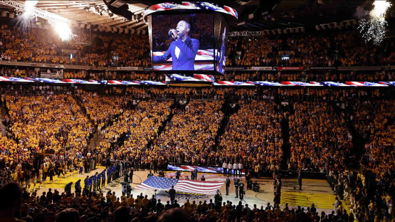 Fans at Oracle Arena watch as musician Aloe Blacc performs the national anthem before Game 7 of basketball's NBA Finals between the Golden State Warriors and the Cleveland Cavaliers in Oakland, Calif., Sunday, June 19, 2016.