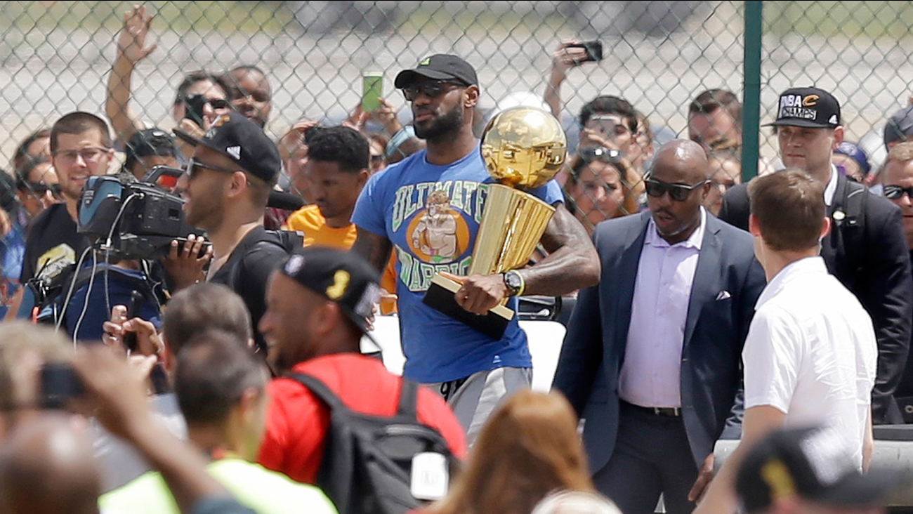 Cleveland Cavaliers' LeBron James carries the NBA Championship trophy after arriving in Cleveland, Monday, June 20, 2016.