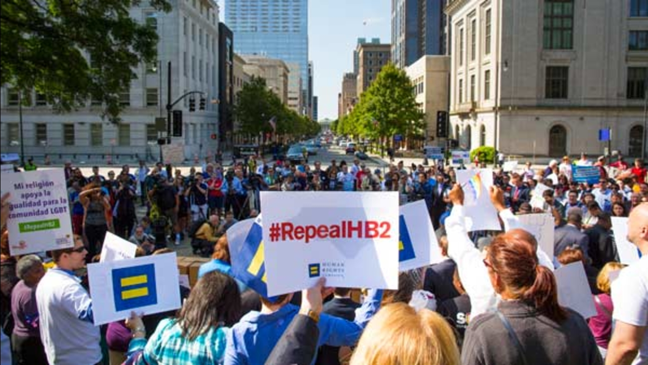 Supporters at a May 2016 rally hold up signs of support during TurnOUT! NC, a joint project to mobilize LGBT and pro-equality North Carolinians.