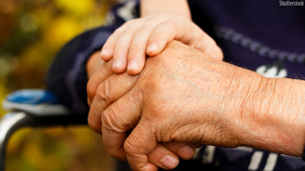 young hand holding elderly one