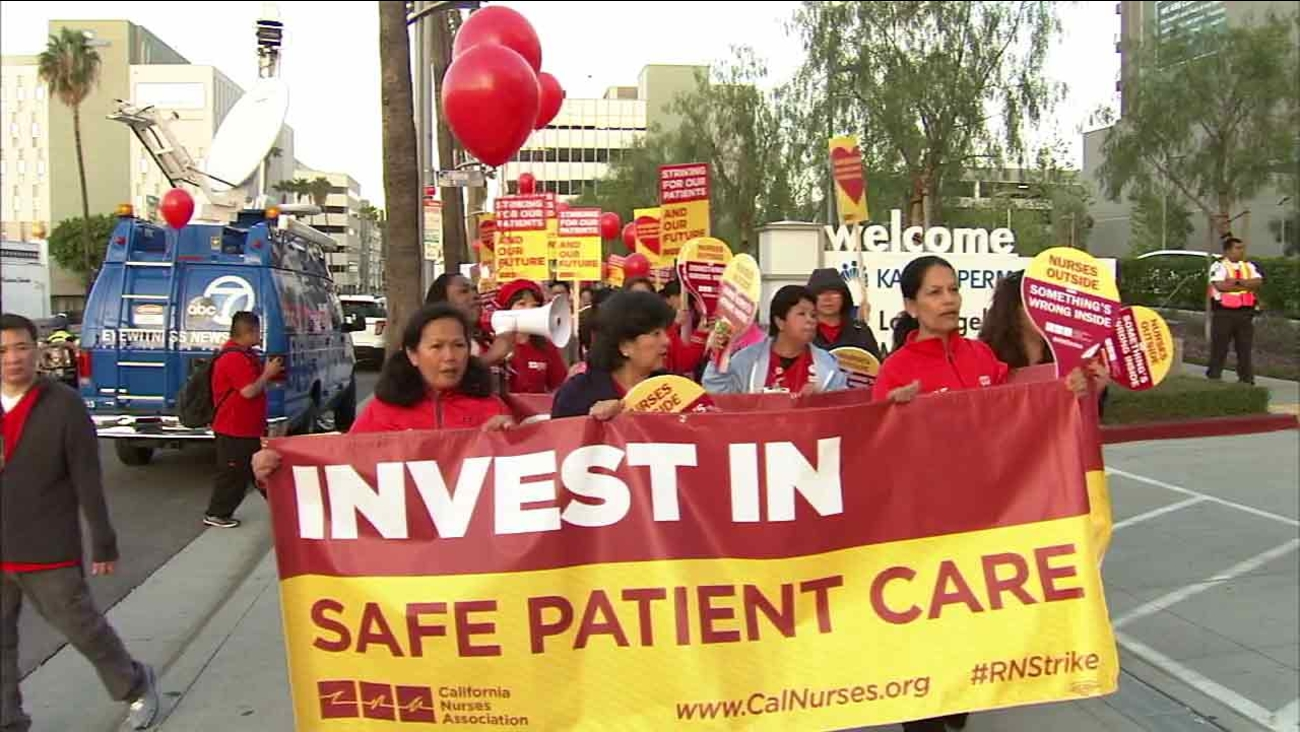 People hold signs during a labor strike by Kaiser Permanente nurses on Tuesday, March 15, 2016.