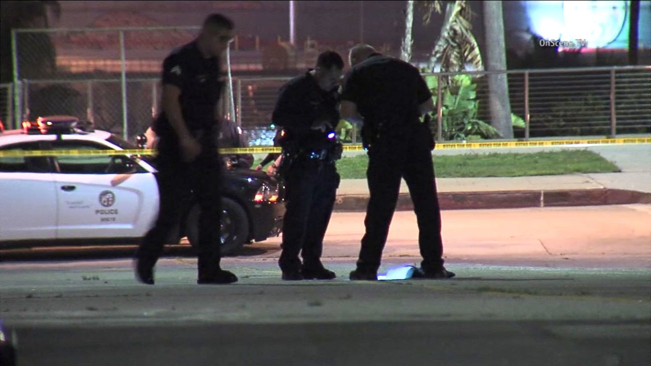 Police examine the scene where a 25-year-old man was gunned down in San Pedro.