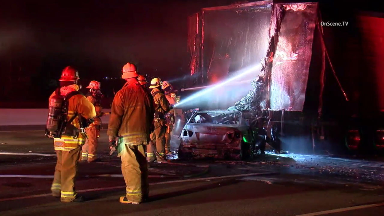 Firefighters work to put out any residual flames after a car and trailer of a big rig burst into flames during a crash on the 101 Freeway in Agoura Hills on Tuesday, June 28, 2016.