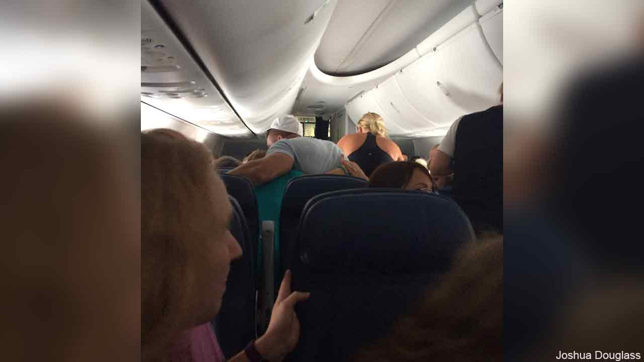 Former NFL quarterback Tim Tebow is seen praying with a family on a flight.