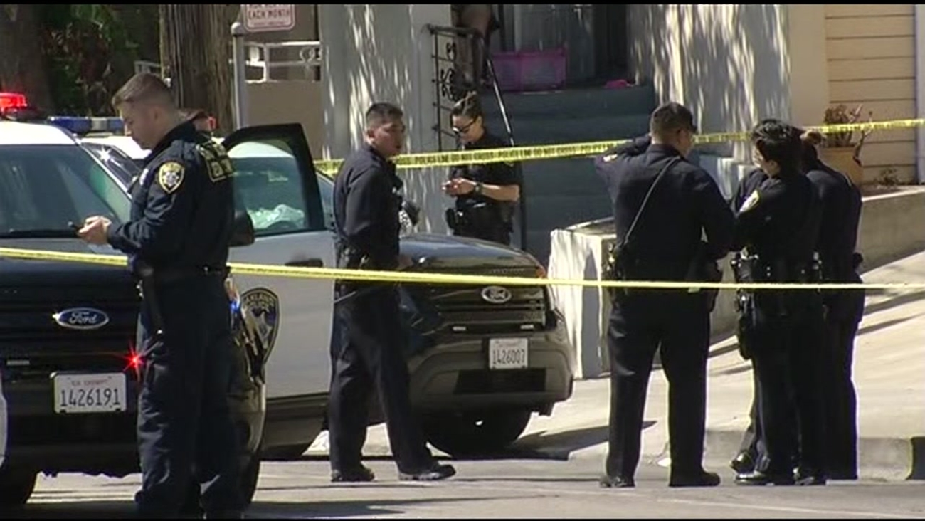The image shows police officers investigating a double homicide near 3300 block of MacArthur in East Oakland on July 2, 2016.  Boulevard.