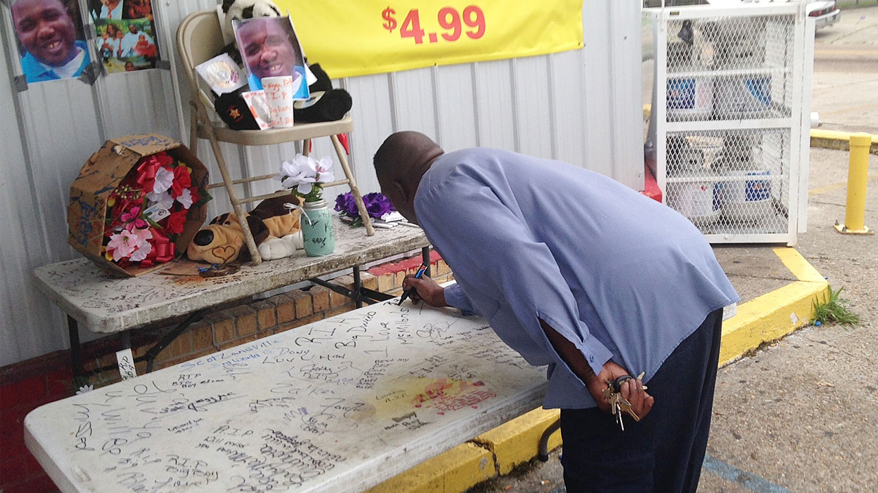 "Arthur Baines signs ""RIP Big Dogg"" on a folding table that Alton Sterling used to sell homemade CDs outside the convenience store, Wednesday, July 6, 2016, in Baton Rouge, La."
