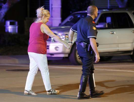 <div class='meta'><div class='origin-logo' data-origin='AP'></div><span class='caption-text' data-credit='AP Photo/Tony Gutierrez'>An unidentified woman and a law enforcement officer hold hands as they walk out of the Baylor University Medical Center</span></div>
