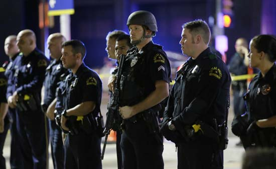 <div class='meta'><div class='origin-logo' data-origin='AP'></div><span class='caption-text' data-credit='AP Photo/LM Otero'>Dallas police officers stand in a line near the site of shootings in downtown</span></div>