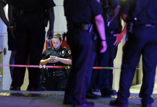 <div class='meta'><div class='origin-logo' data-origin='AP'></div><span class='caption-text' data-credit='AP Photo/Tony Gutierrez)'>A Dallas police officer uses her smart device as she and other emergency responders stand outside the emergency room at Baylor University Medical Center</span></div>
