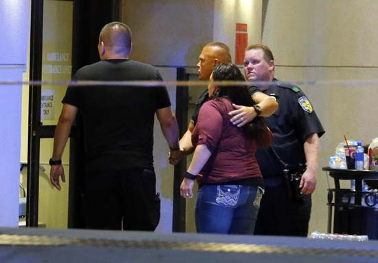 <div class='meta'><div class='origin-logo' data-origin='AP'></div><span class='caption-text' data-credit='AP Photo/Tony Gutierrez'>Law enforcement officials escort a couple in through the emergency room entrance at Baylor University Medical Center</span></div>