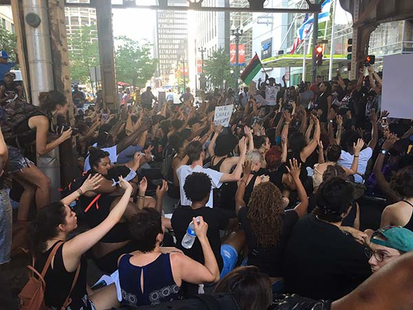 <div class='meta'><div class='origin-logo' data-origin='WLS'></div><span class='caption-text' data-credit=''>Protesters at State and Lake chant &#34;Hands up, don't shoot,&#34; Monday evening.</span></div>
