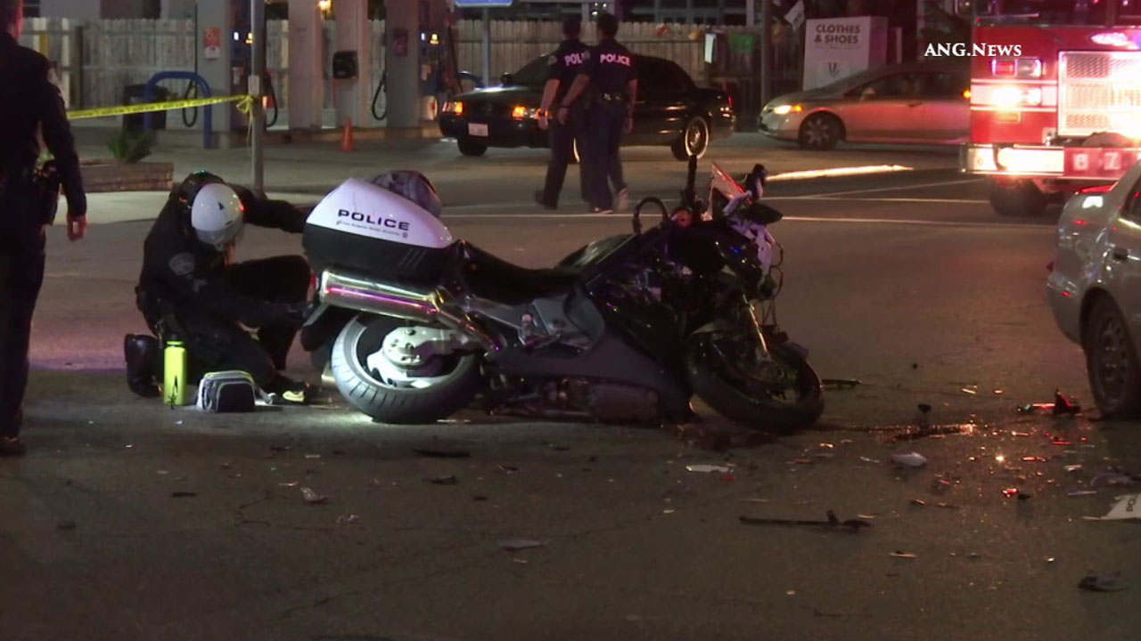 Authorities look at the damage to a motorcycle after an LAX police officer was hurt in a hit-and-run crash on Tuesday, July 12, 2016.