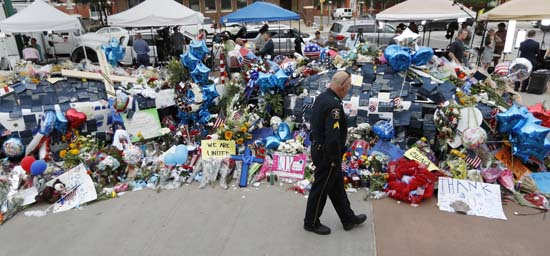 <div class='meta'><div class='origin-logo' data-origin='AP'></div><span class='caption-text' data-credit='AP Photo/Eric Gay'>A policeman visits a makeshift memorial at the Dallas police headquarters</span></div>