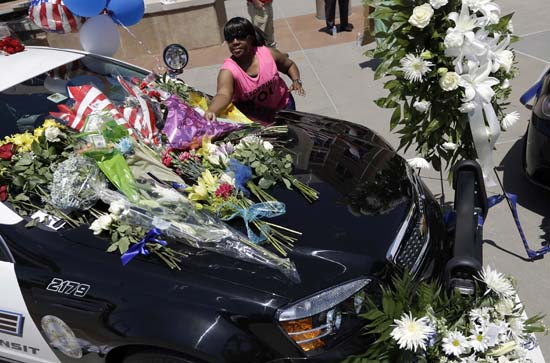 <div class='meta'><div class='origin-logo' data-origin='AP'></div><span class='caption-text' data-credit='AP Photo/Eric Gay'>In this Friday, July 8, 2016 file photo, Cynthia Ware places flowers on a make-shift memorial at the Dallas police headquarters</span></div>