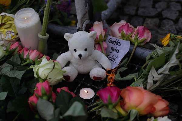 <div class='meta'><div class='origin-logo' data-origin='none'></div><span class='caption-text' data-credit='Markus Schreiber/AP Photo'>A teddy bear and candles sit between flowers to commemorate the victims of an attack in the France city Nice in front of the French embassy in Berlin, Germany, Friday, July 15, 201</span></div>