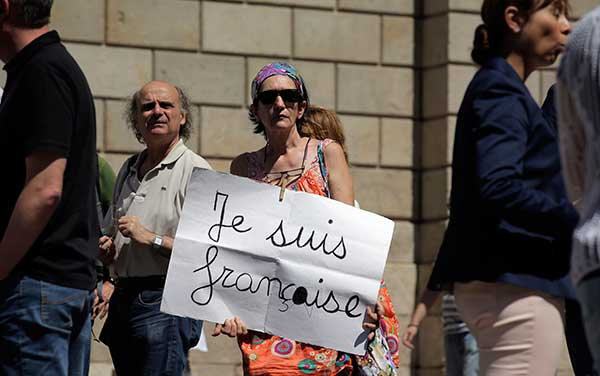 <div class='meta'><div class='origin-logo' data-origin='none'></div><span class='caption-text' data-credit='Manu Fernandez/AP Photo'>A woman holds a banner during a minute of silence in honor of the victims of the Bastille Day tragedy in Nice, in Barcelona, Spain, Friday, July 15, 2016.</span></div>