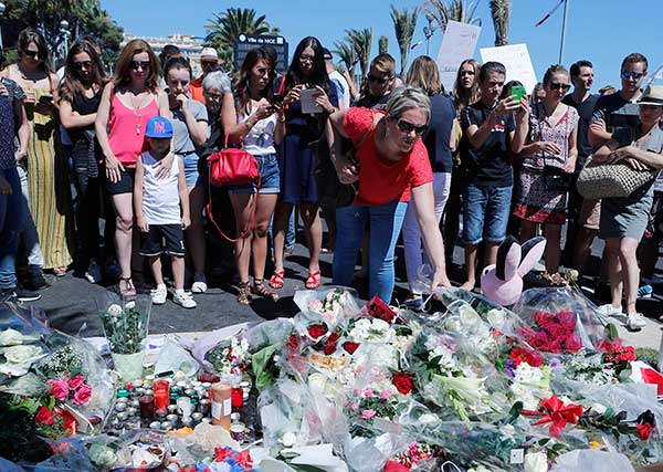 <div class='meta'><div class='origin-logo' data-origin='none'></div><span class='caption-text' data-credit='Francois Mori/AP Photo'>A woman puts flowers near the scene where a truck mowed through revelers in Nice, southern France, Friday, July 15, 2016.</span></div>