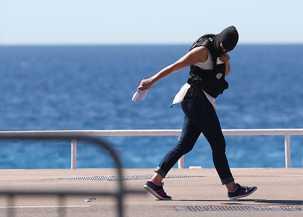 <div class='meta'><div class='origin-logo' data-origin='none'></div><span class='caption-text' data-credit='/AP Photo'>A forensic police woman walks at the scene of an attack after a truck plowed through a crowd in Nice, southern France, Friday, July 15, 2016.</span></div>