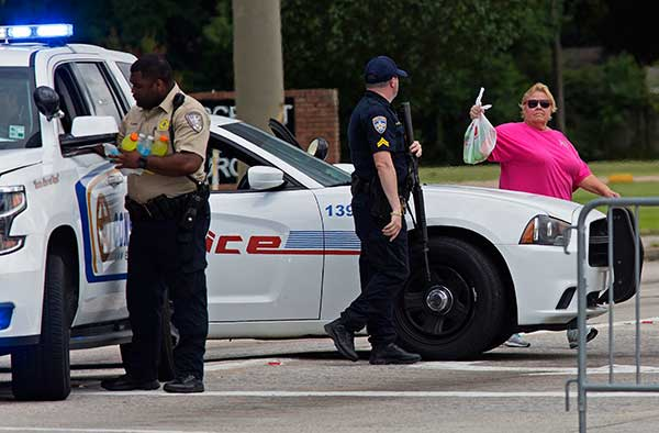 <div class='meta'><div class='origin-logo' data-origin='none'></div><span class='caption-text' data-credit='Max Becherer/AP Photo'>A citizen brings cold drinks and snacks to a Baton Rouge Police officer manning a road block on Old Hammond Highway near the intersection with Airline Highway on Sunday.</span></div>