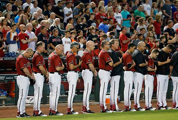 <div class='meta'><div class='origin-logo' data-origin='none'></div><span class='caption-text' data-credit='Ross D. Franklin/AP Photo'>Arizona Diamondbacks players and coaches bow their heads during a moment of silence for the slain Baton Rouge, La,, police officers killed.</span></div>
