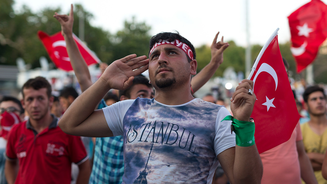 A protester salutes as he takes part in a rally in Taksim Square, Istanbul, Sunday, July 17, 2016.