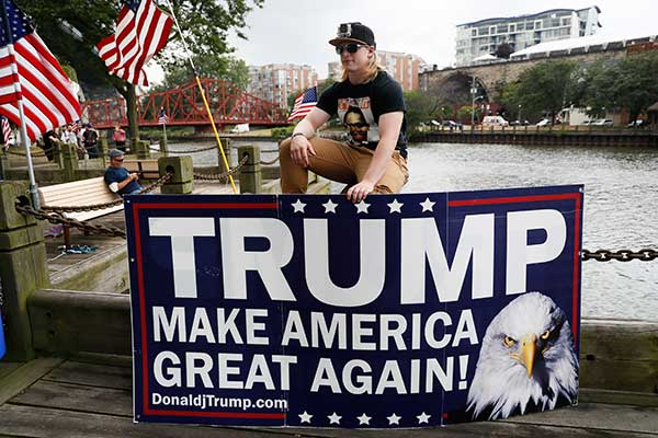 <div class='meta'><div class='origin-logo' data-origin='none'></div><span class='caption-text' data-credit='John Minchillo/AP Photo'>Tyler Sheets sits with a sign as he rallies for Republican presidential candidate Donald Trump at Settlers Landing Park on Monday, July 18, 2016, in Cleveland.</span></div>