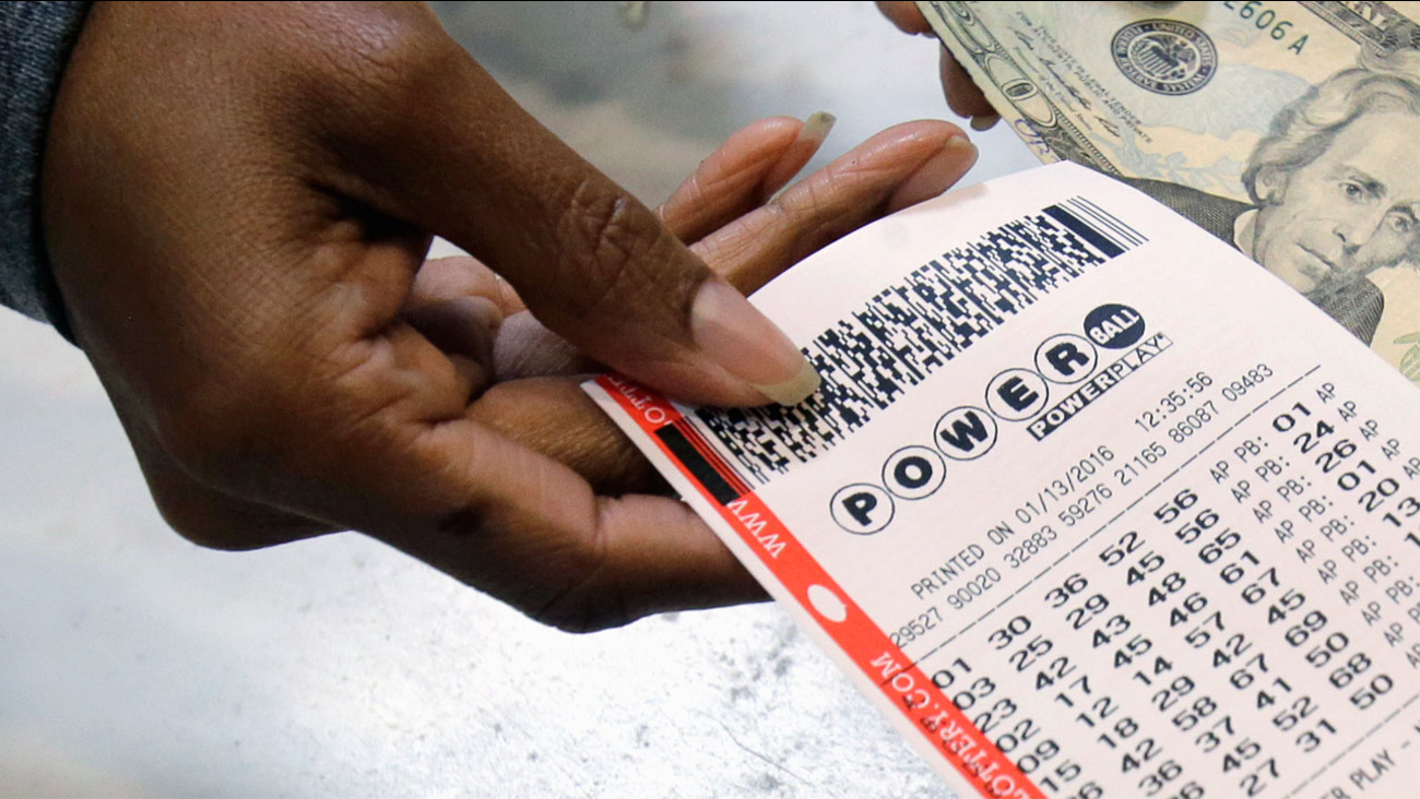 In this Jan. 13, 2016 file photo, a clerk hands over a Powerball ticket for cash at Tower City Lottery Stop in Cleveland.