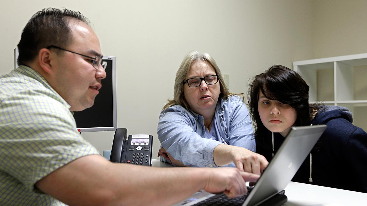 FILE - Enrollment counselor Vue Yang, left, goes over some of the health insurance plans available to Laura San Nicolas