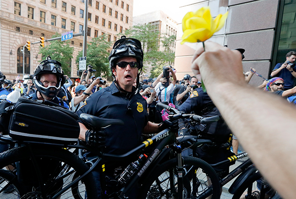 <div class='meta'><div class='origin-logo' data-origin='AP'></div><span class='caption-text' data-credit='John Minchillo/AP'>A protesters holds a flower during a clash with police on Tuesday, July 19, 2016, in Cleveland, during the second day of the Republican convention.</span></div>