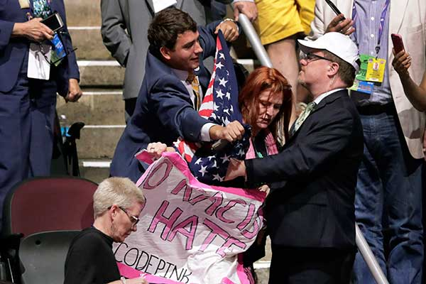 <div class='meta'><div class='origin-logo' data-origin='none'></div><span class='caption-text' data-credit='J. Scott Applewhite/AP Photo'>A convention attendee tries to cover a Code Pink activist with a U.S. Flag during the second day of the Republican National Convention in Cleveland, Tuesday, July 19, 2016.</span></div>