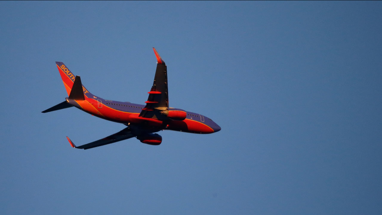 A Southwest Airlines plane flies in late evening light above Seattle, Saturday, July 2, 2016, in Seattle. (AP Photo/Ted S. Warren)