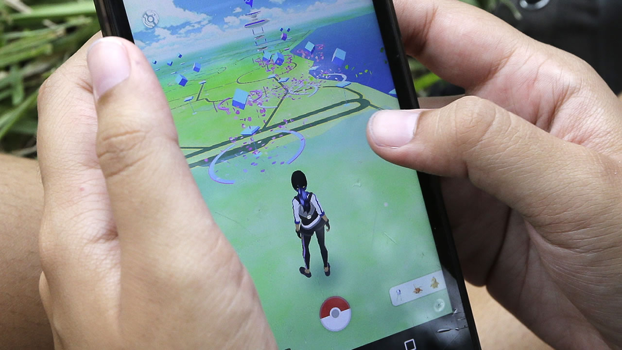 A Pokemon Go player checks her position as she looks for Pokemon, Tuesday, July 12, 2016, at Bayfront Park in downtown Miami. (AP Photo/Alan Diaz)
